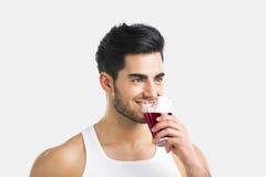 Uomo atletico che beve un succo immagini stock
