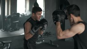 Uomo atletico che combatte durante l'addestramento con l'istruttore di pugilato alla palestra movimento lento 4k video d archivio
