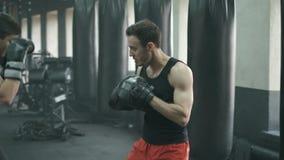 Uomo atletico che combatte durante l'addestramento con l'istruttore di pugilato alla palestra movimento lento 4k archivi video