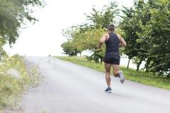 Uomo atletico che corre in salita, all'aperto immagine stock