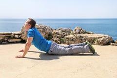 Uomo atletico che fa allungando esercizio, preparante per l'allenamento sulla spiaggia Atleta bello di forma fisica che fa una ro Immagini Stock Libere da Diritti