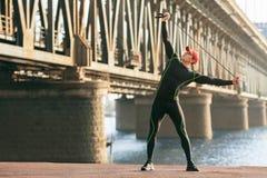 Uomo atletico che fa allungando gli esercizi, all'aperto Esterno risolvente maschio attivo sui precedenti del ponte Fotografia Stock Libera da Diritti