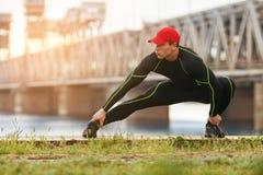 Uomo atletico che fa allungando gli esercizi, all'aperto Esterno risolvente maschio attivo sui precedenti del ponte Fotografia Stock
