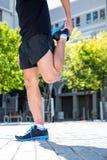 Uomo atletico che fa un allungamento della gamba Fotografia Stock Libera da Diritti