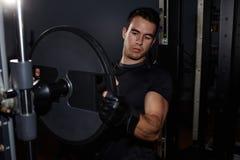 uomo atletico che prepara la macchina della palestra per l'allenamento Immagine Stock