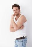 Uomo atletico che si leva in piedi alla parete in maglietta Fotografie Stock