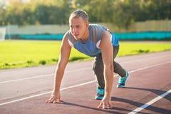 Uomo atletico che sta nella posizione pronta a funzionare su una pedana mobile Fotografia Stock