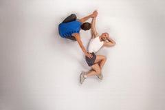 uomo atletico che streching con l'addestratore personale Fotografie Stock
