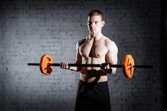 Uomo atletico del culturista brutale con l'ABS, le spalle, il bicipite, il tricipite e l'allenamento perfetti dei bilancieri di D Fotografie Stock