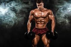 Uomo atletico del forte culturista muscolare brutale che pompa sui muscoli con la testa di legno su fondo nero workout fotografia stock libera da diritti