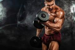 Uomo atletico del forte culturista muscolare brutale che pompa sui muscoli con la testa di legno su fondo nero workout immagine stock libera da diritti