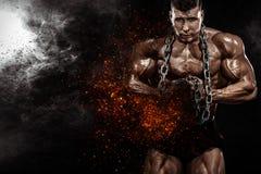 Uomo atletico del forte culturista muscolare brutale che pompa sui muscoli con le catene su fondo nero Culturismo di allenamento fotografie stock libere da diritti
