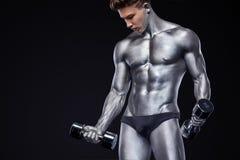 Uomo atletico del forte culturista muscolare brutale che pompa sui muscoli con le teste di legno su fondo nero workout immagine stock libera da diritti