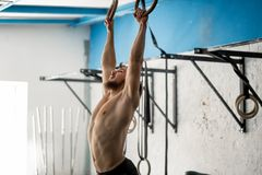 Uomo atletico di esercizio del muscolo-su che fa allenamento intenso alla palestra sugli anelli relativi alla ginnastica Immagini Stock
