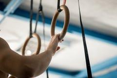 Uomo atletico di esercizio del muscolo-su che fa allenamento intenso alla palestra sugli anelli relativi alla ginnastica Immagini Stock Libere da Diritti