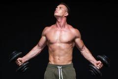 Uomo atletico di potere bello con la testa di legno che guarda con confidenza in avanti Forte culturista con gli addominali scolp immagini stock libere da diritti