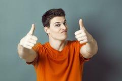 Uomo atletico dubbio con la maglietta ed i pollici arancio su per successo fotografie stock libere da diritti