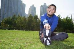 Uomo atletico sorridente dei giovani che allunga nell'orizzontale del parco di Pechino Immagine Stock Libera da Diritti