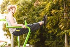Uomo attivo che si esercita sull'aumento della gamba all'aperto Fotografia Stock
