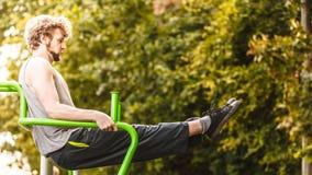 Uomo attivo che si esercita sull'aumento della gamba all'aperto Immagini Stock Libere da Diritti