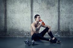 Uomo attivo con la bottiglia di acqua e il dumbell Fotografie Stock Libere da Diritti