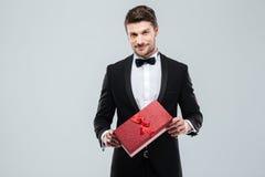 Uomo attracive sicuro in contenitore di regalo di condizione e della tenuta dello smoking Immagini Stock