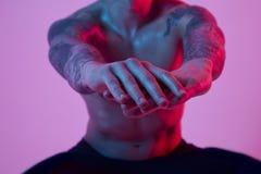 Uomo attraente adatto di sport che fa edificio occupato, mani stese Luce istantanea dello studio di colore Fotografia Stock