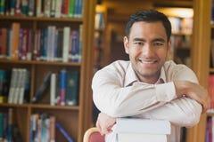 Uomo attraente allegro che posa appoggiandosi una pila di libri in biblioteca Fotografia Stock