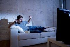 Uomo attraente a casa che si trova sullo strato alla partita di sport di sorveglianza del salone sulla TV che celebra scopo Fotografia Stock