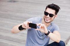 Uomo attraente che cattura le foto con uno smartphone Fotografia Stock Libera da Diritti