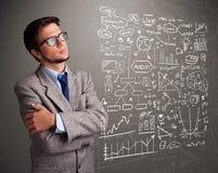 Uomo attraente che esamina i grafici ed i simboli del mercato azionario Immagine Stock Libera da Diritti
