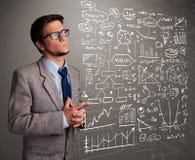 Uomo attraente che esamina i grafici ed i simboli del mercato azionario Fotografia Stock