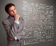 Uomo attraente che esamina i grafici ed i simboli del mercato azionario Immagini Stock