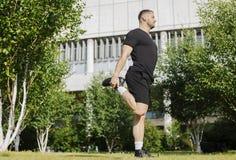 Uomo attraente che fa allungando gli esercizi di gambe con le mani in parco Immagini Stock