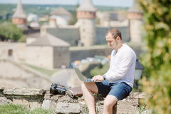 Uomo attraente che lavora con il computer portatile nel parco Immagini Stock Libere da Diritti