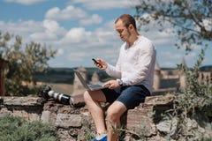 Uomo attraente che lavora con il computer portatile nel parco Immagine Stock