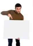 Uomo attraente che mostra e che indica tabellone per le affissioni in bianco Fotografia Stock