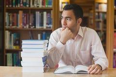 Uomo attraente che si siede nella biblioteca davanti ad un libro aperto Fotografia Stock