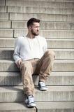 Uomo attraente che si siede sulle scale Immagine Stock