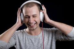Uomo attraente che sorride e che ascolta la musica sulle cuffie con Fotografia Stock Libera da Diritti