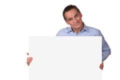 Uomo attraente che tiene segno bianco in bianco Fotografie Stock Libere da Diritti