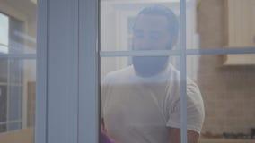 Uomo attraente con la bella barba dei pantaloni a vita bassa che pulisce la finestra in guanti con il detersivo nella sua nuova c video d archivio