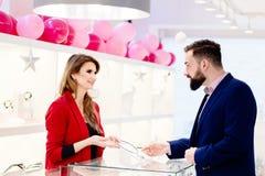 Uomo attraente con una barba che sceglie un regalo della collana in gioielleria Fotografie Stock Libere da Diritti