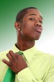 Uomo attraente in cravatta di registrazione verde sopra priorità bassa verde immagini stock