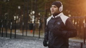 Uomo attraente in cuffie che fanno esercizio di riscaldamento che prepara per pareggiare mentre musica d'ascolto nel parco di inv Immagini Stock Libere da Diritti