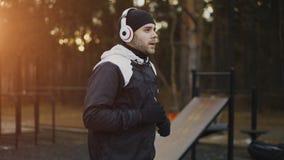 Uomo attraente in cuffie che fanno esercizio di riscaldamento che prepara per pareggiare mentre musica d'ascolto nel parco di inv Fotografia Stock