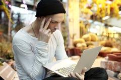 Uomo attraente dei pantaloni a vita bassa che lavora al computer portatile moderno Sedendosi in un giorno soleggiato del parco ve Immagini Stock