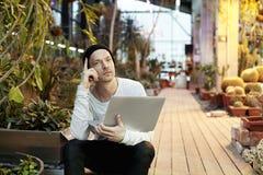 Uomo attraente dei pantaloni a vita bassa che lavora al computer portatile moderno Sedendosi in un giorno soleggiato del parco ve Immagine Stock Libera da Diritti