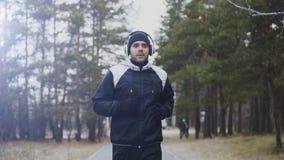 Uomo attraente del corridore in cuffie che pareggiano mentre musica d'ascolto nel parco di inverno di mattina Immagine Stock