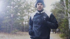 Uomo attraente del corridore in cuffie che pareggiano mentre musica d'ascolto nel parco di inverno di mattina Fotografia Stock Libera da Diritti